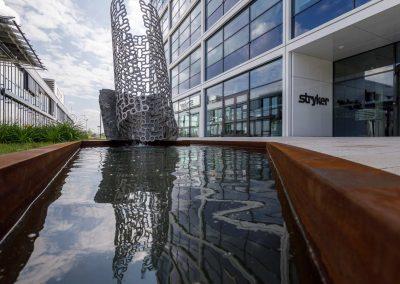 Eingang zu Firmengebäude mit Wasserskulptur